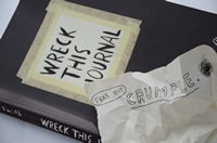 A small black paperback book with the title wreck this journal. A crumpled paper sits on top