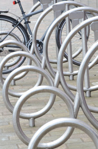 A series of metal circles that form a bike rack with one bike at the far end.