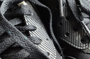 Pair of black trainers seen close up by the laces