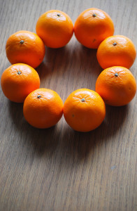 8 small oranges arranged in a circle on a wooden table top