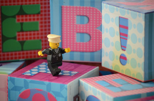 A small lego figure marching across some alphabet blocks towards the right