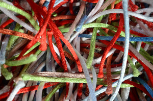 a jumble of bright colour synthetic threads on a rug
