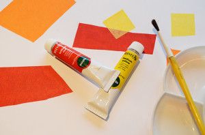 White background with red and yellow shapes. Yellow paintbrush and palette lower left. REd and yellow paint tubes in the middle