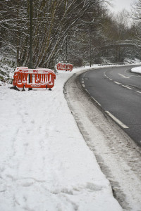 Red plastic barriers around lamposts in the snow by the side of a curving road