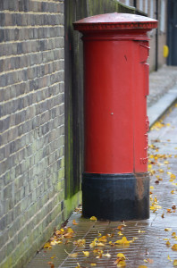 Red letterbox on a wet day with leaves on the foor
