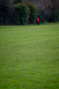Long shot across a park towards a small figure in a red jacket with his back to the camera