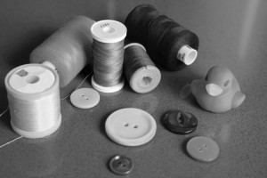 Still life of different coloured cottons and buttons with a small yellow duck