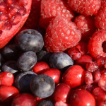 Close up of a bowl of berries - strawberries, raspeberries, pomegranate seeds and blueberries