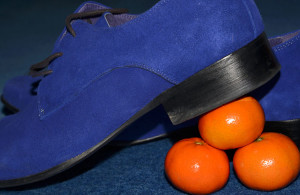Bright blue suede shoe with its heel balanced on 3 satsumas