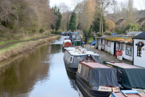 Looking down a river with canal boats moored along the right hand side