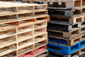 Two stacks of bare wooden pallets stacked on top of one another with one blue pallet on the bottom of the second pile