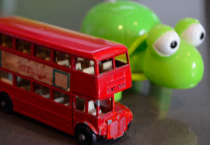 Toy double decker bus beside a bright green wind up tortoise